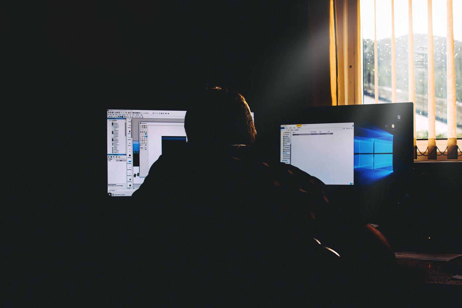 Man sat in the dark looking at computer